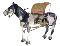 Blowtorch, a life size black and white mechanical horse with its central panel open to show the interior engine.