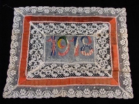 "A white and orange lace handkerchief with embroidered inscription ""1918 Souvenir de France."""