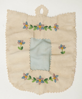 A handcrafted light rose coloured cloth picture frame embroidered with bright blue and pink flowers.