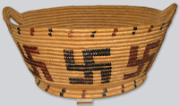 An oval shaped basket with handles in traditional Salish cedar weaving style, decorated with distinctive swastika designs indicating faith and luck.