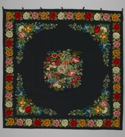 Large square black wool tablecloth with realistic floral embroidery forming a border and central bouquet. Primary colours are red, orange, and yellow.