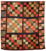 A large quilt with checkerboard squares of warm, reddish colours made by Clara Bowman, circa 1920.
