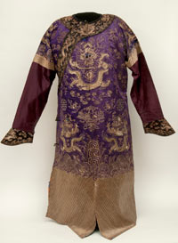 Opulent purple silk robe with intricate designs in couched gold thread worn during the Qing dynasty (1644–1911) by the Imperial family.