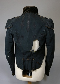 A dark green wool and velvet tunic with brass buttons, attributed to Donald McDougald.