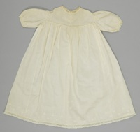 A small, slightly yellowed white dress with lace trim at the sleeves and neckline and embroidered flowers and French knots on the chest.