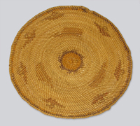 A round mat woven of golden brown grass using a distinctive weaving method that mimics the sun with lines radiating from the centre.