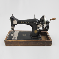 A black Singer 128 model hand-cranked sewing machine known for being light, portable, and suitable for homes without electricity.