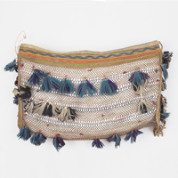 A handheld bag made of netted caribou-hide babiche and decorated with ribbon appliqué and blue wool tassels, made in Lutselk'e.