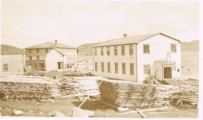 The Machine Shop and Grenfell Mission Store in St. Anthony, Newfoundland, surrounded by piled lumber.