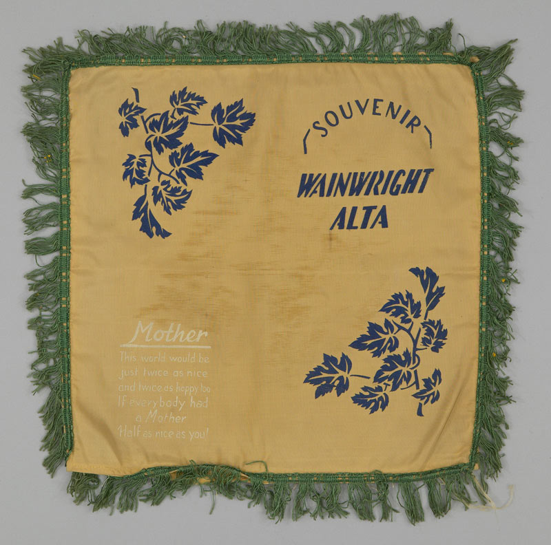 An aged tan pillow case with green tassel trim, printed with two clusters of maple leaves in blue and a small Mother poem in white text.