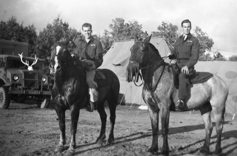 Two male uniformed RCAF members on horses pose in front of tents and a jeep with antlers planted on the hood.