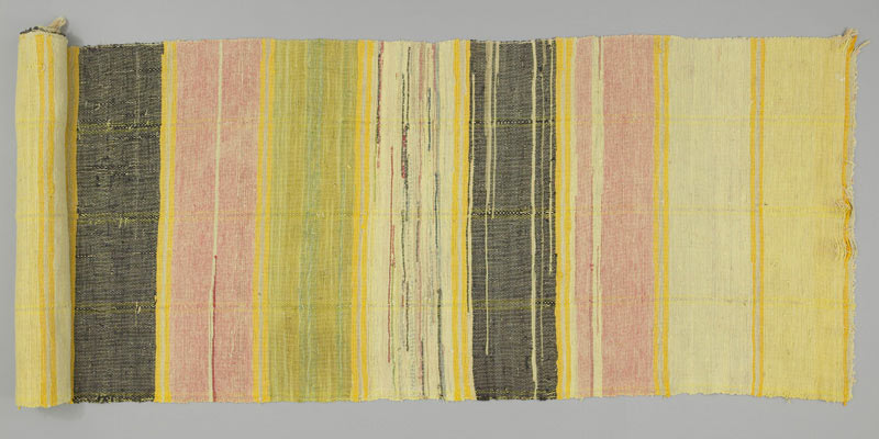 A long and narrow rug, rolled at the left end, with wide, irregular yellow, pink, green and black horizontal stripes.