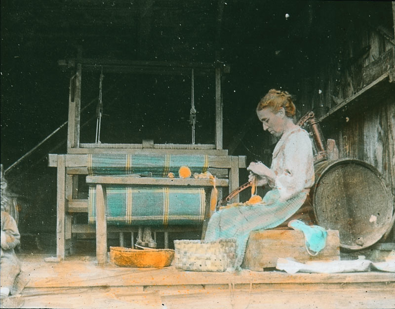 Archival photograph in colour, depicting a seated woman preparing yellow rags next to a loom, circa 1930.
