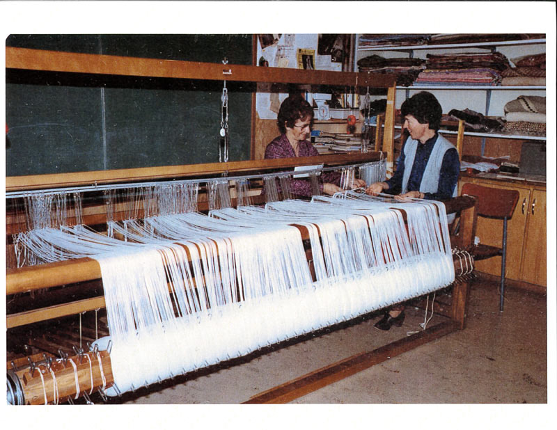 Two women smile as they near the end of threading a white warp on a 100-inch loom.