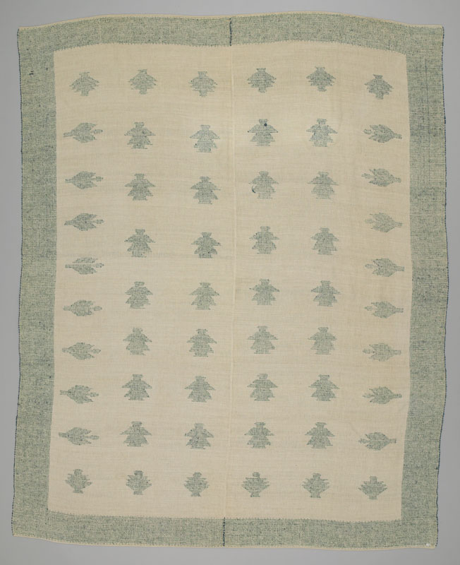 Rear view of a green and white blanket with simplistic female figures in a grid, bordered on all four sides by pine trees.