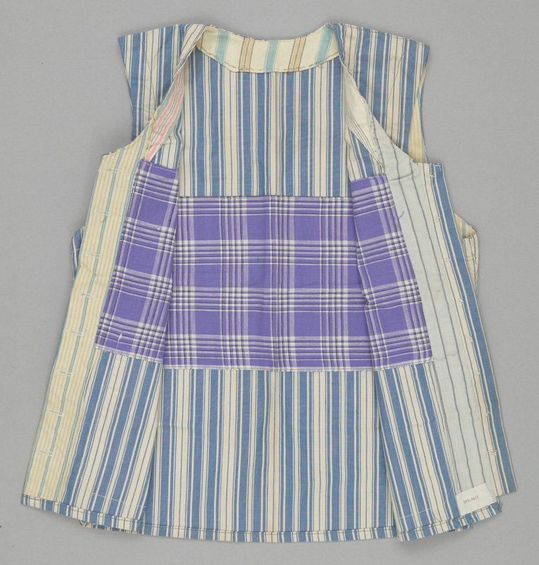 Interior view of a button-up vest made from vertically striped blue and white fabric, showing different coloured scraps used for the lining.