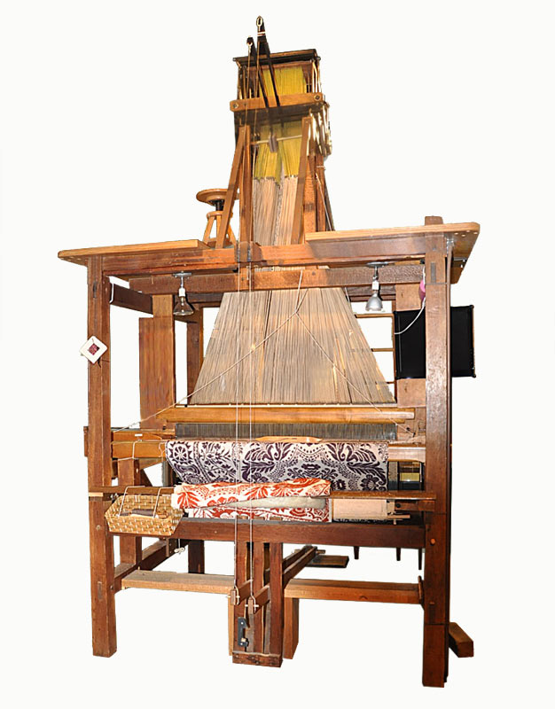 John Campbell's large wooden jacquard loom with red and purple coverlets visible.
