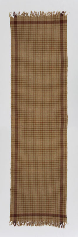 An olive green rectangular wool shawl with a plaid pattern formed by lines in shades of brown and red.