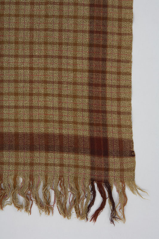 Detail view of an olive green rectangular wool shawl with a plaid pattern formed by lines in shades of brown and red.