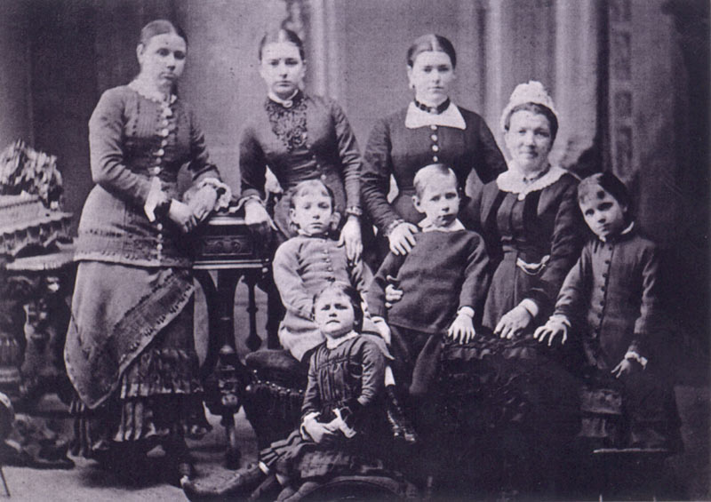 A posed portrait of an older woman surrounded with children of varying ages, all in fancy dress.