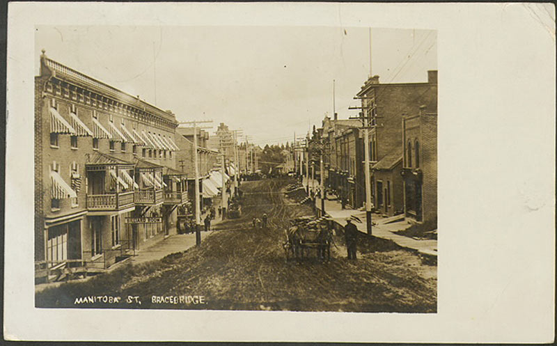 A postcard looking down Manitoba Street, Bracebridge at storefronts and a horse-drawn carriage, 1910.