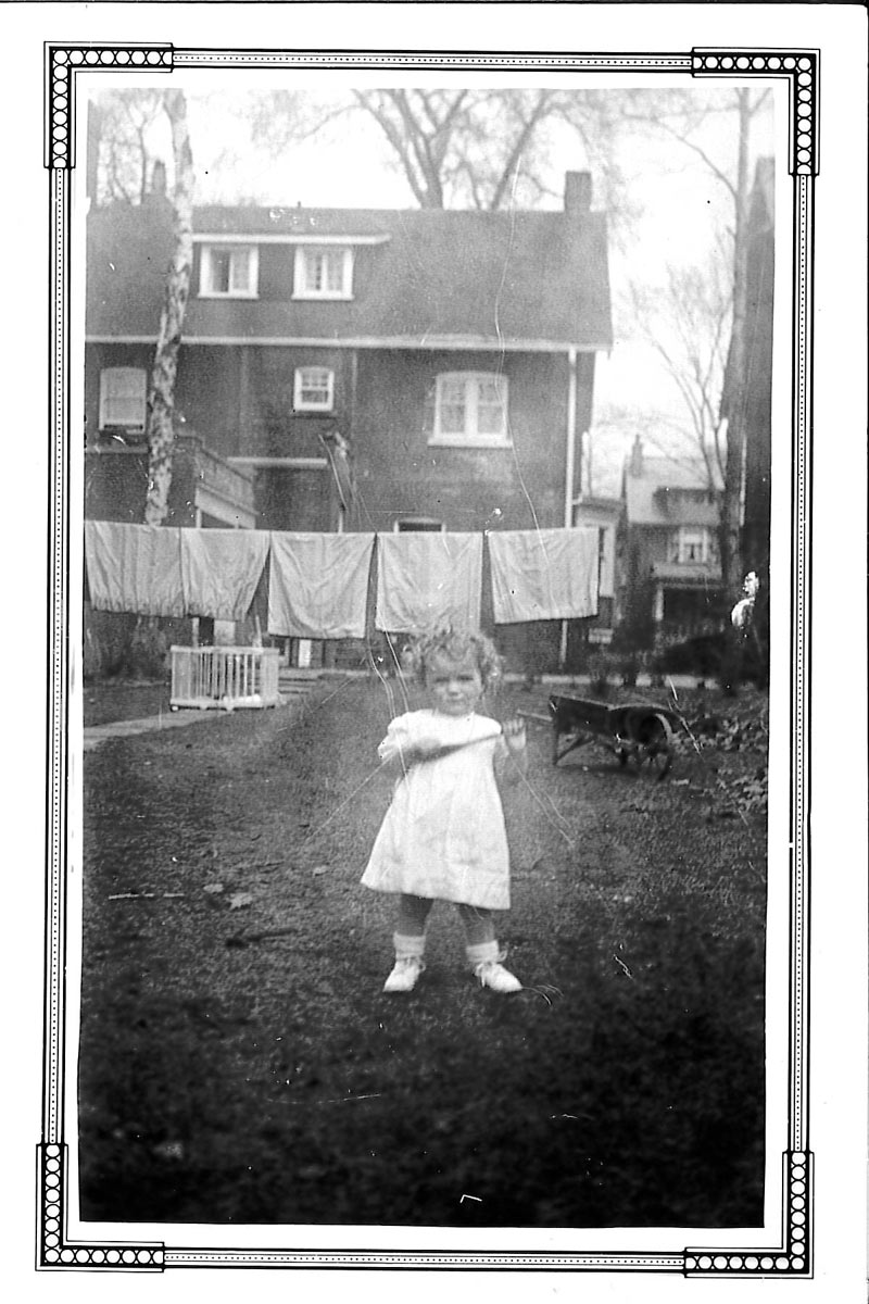 Young Anne Angus wearing the dress, standing in front of laundry in the backyard of a house.