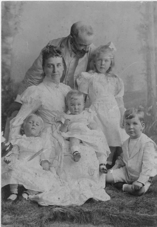 A mother and father pose for a portrait surrounded by their four children, all dressed in white.