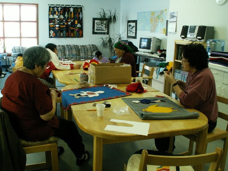 Women gathered around a table working on hangings like this one.