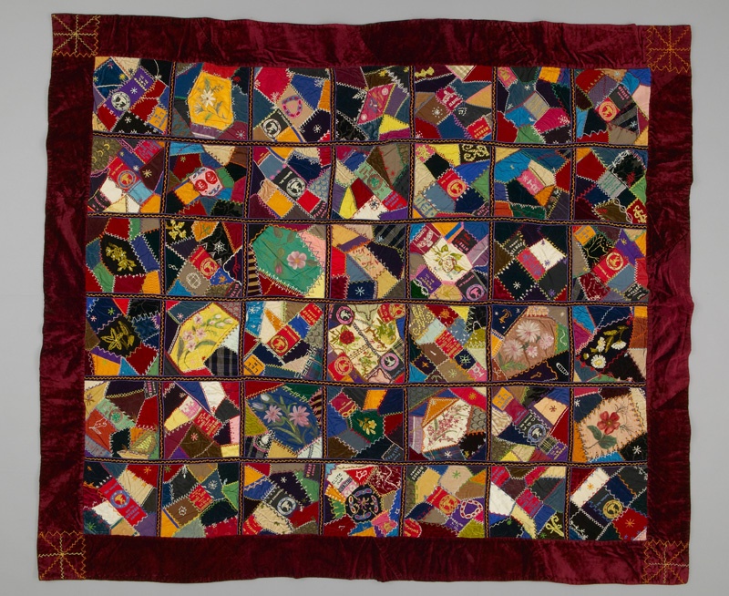 A busy, colourful quilt with a 7 by 6 grid bordered by red velvet.