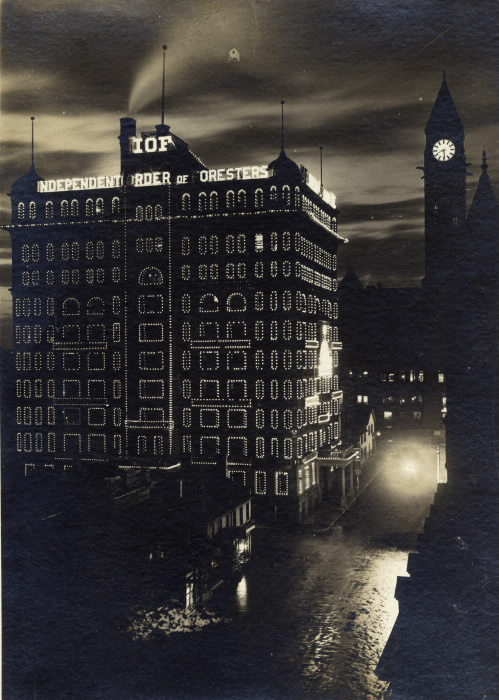The Independent Order of Foresters building at night with its sign and windows illuminated.