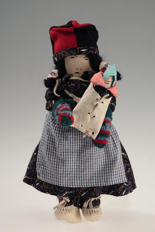 Small doll in a dress and apron, wearing a bonnet and carrying a baby.