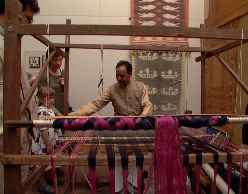 Meher demonstrating ikat weaving to three onlookers on a loom with a striking pink and purple dyed warp.