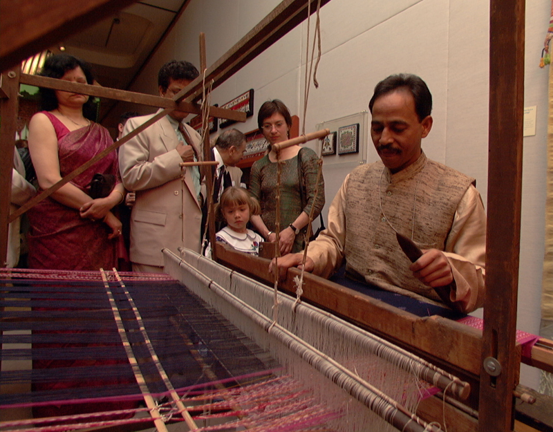 A view showing the warp and a hint of the pink and purple sari Meher is weaving in front of a crowd.