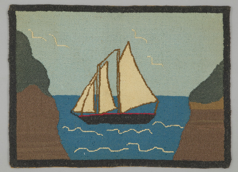 Rug hooking of a schooner with four sails on the water flanked by shoreline and with gulls flying overhead.