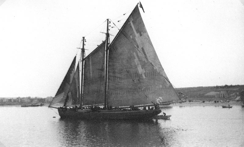 A Labrador fishing schooner with many people aboard and heavily patched sails in Bay Roberts, 1926.