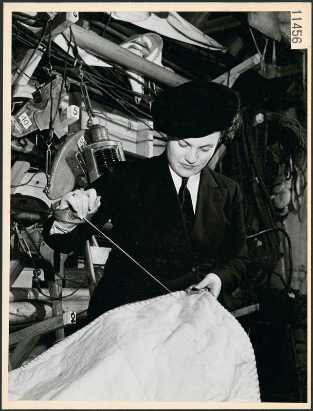 Gwynneth Speedie in a sail loft wearing a sailmaker's palm as she repairs a sail, 1945.