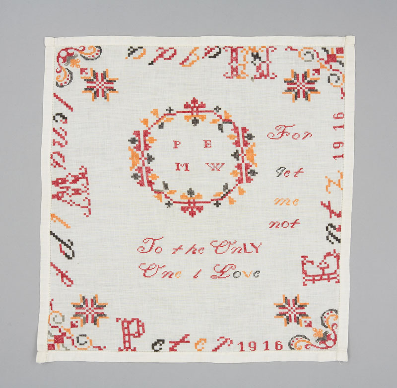 A square white cotton handkerchief embroidered with red, yellow and green thread in cursive writing.