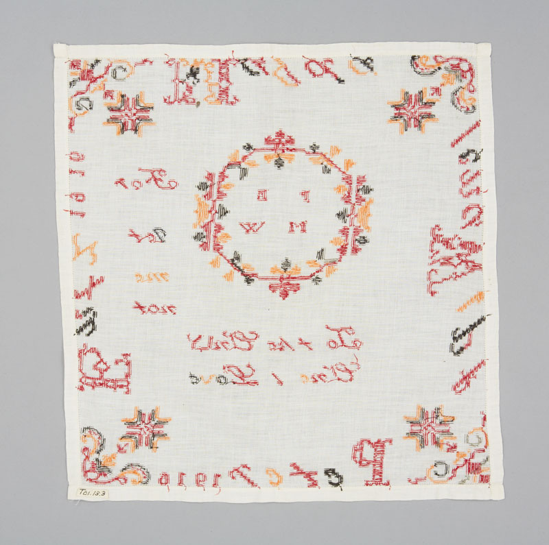 Rear view of a square white cotton handkerchief embroidered with red, yellow and green thread in cursive writing.
