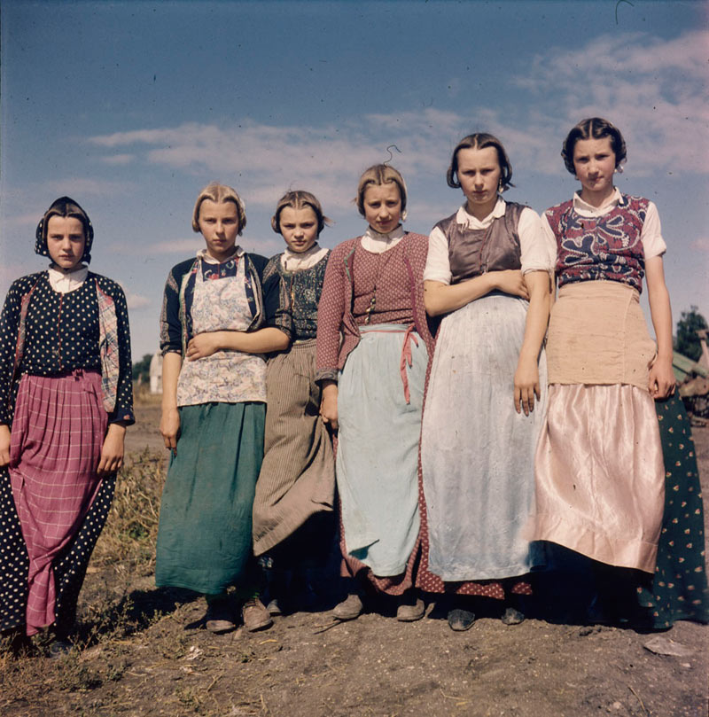 Six young Hutterite girls in dresses and aprons all wearing their hair in a traditional style, 1954.
