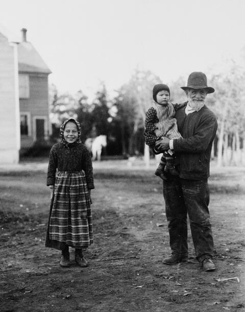 An older man with a white beard holds a young child while a young, smiling girl stands near.