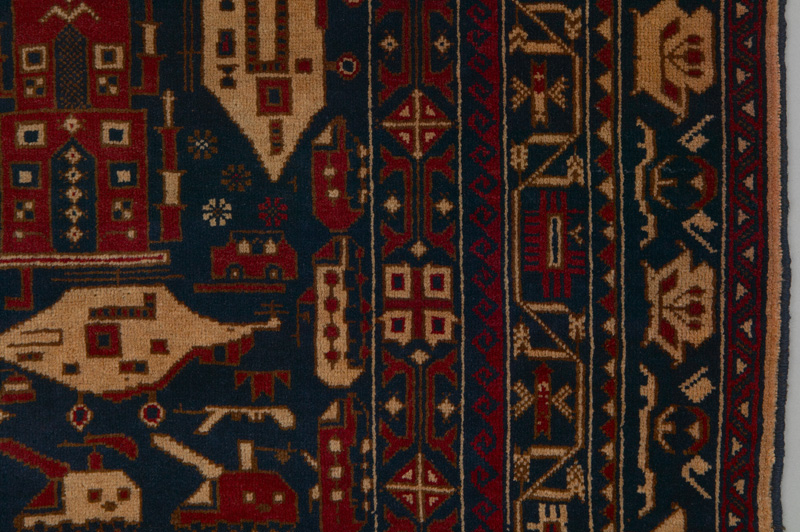 A detailed view of a darkly coloured red and blue rug showing depictions of weapons, battles, and destruction reflecting conflict in Afghanistan.
