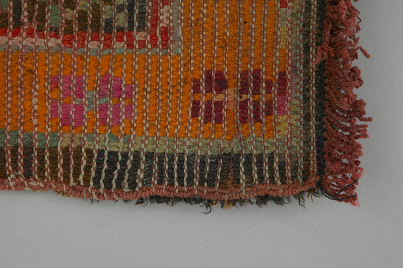 Rear view of a floor rug decorated with geometric shapes and hues of orange, brown and turquoise showing a traditional Doukhobor technique.