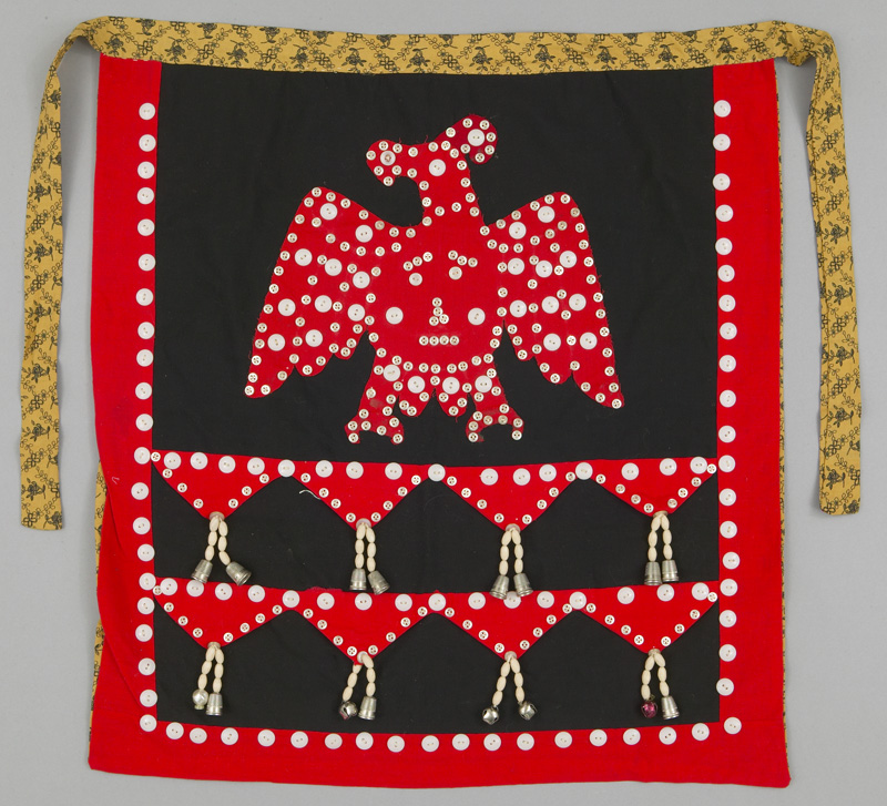 Square ceremonial dance apron with white buttons that secure a red thunderbird crest on black background and bells and thimbles as decorative noisemakers.