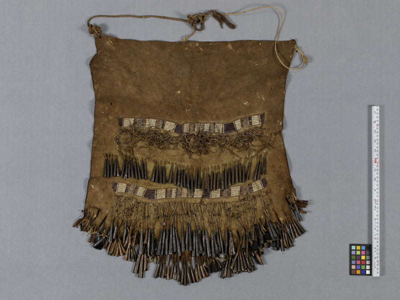 Traditional brown dance apron made from moose skin, with porcupine quill, metal, deer hoof noisemakers.
