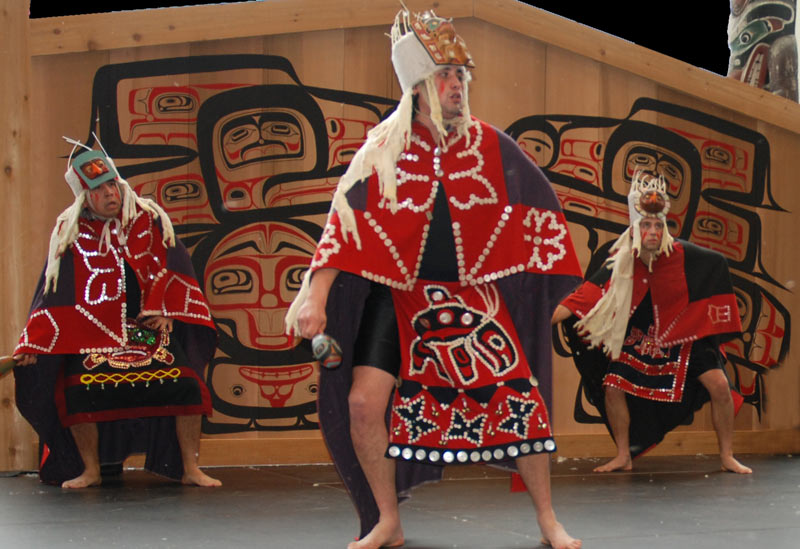 Three men wearing traditional dance coloured aprons performing on stage at a Coastal First Nations Dance Festival.
