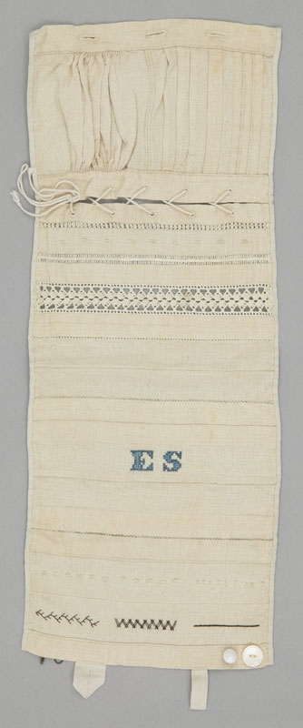 A tall rectangular white cotton sampler demonstrating a number of sewing techniques in horizontal strips and embroidered with the initials 'E.S'.