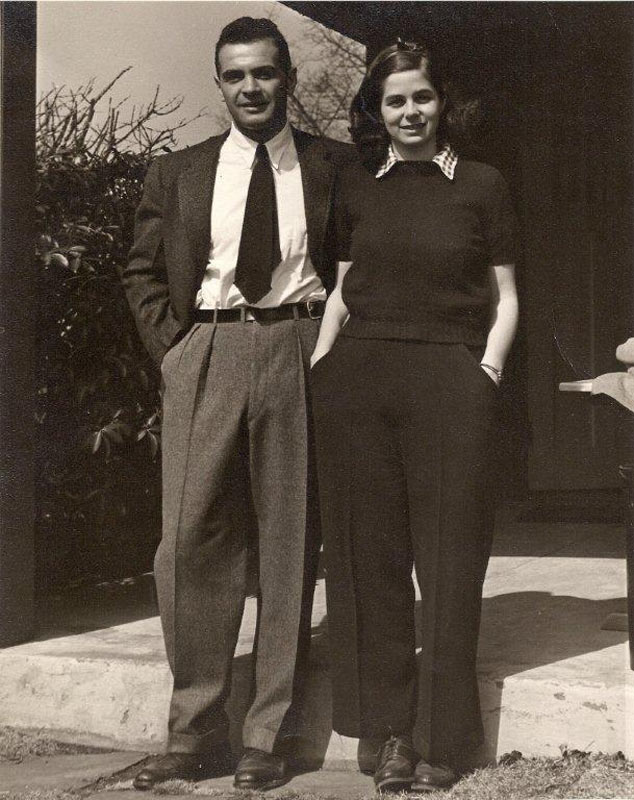 Ann and Maynard Gertler stand embracing on a farmhouse porch as young adults, smiling at the camera.