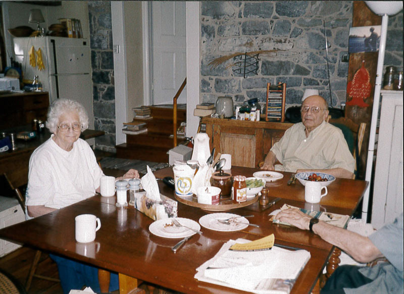 Ann and Maynard Gertler as an elderly couple seated around a dinner table at home, Ann smiling at camera.