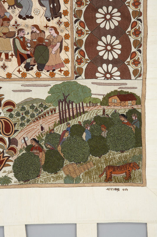 A detail of a large textile embroidery depicting scenes during the reign of George V (1910–1936) in India, showing a community working in a field.