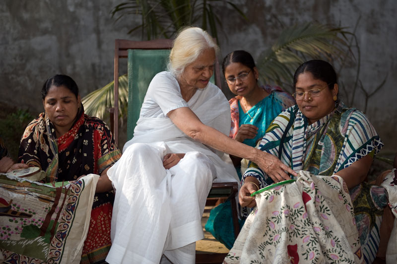 Four women skillfully working on colourful embroidery projects. An elderly Surayia Rahman instructs at center.